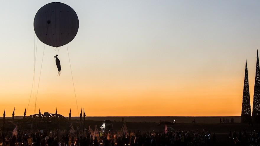 A hot air balloon lifts an acrobat into the sky.