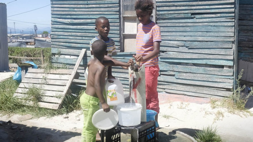 Children at a public water tap (emthonjeni) in Monwabisi Park, Khayelitsha