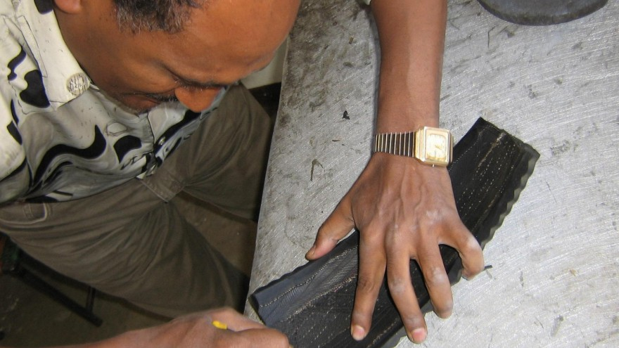 An artisan at soleRebels cuts the sole for a shoe out of an old car tyre.