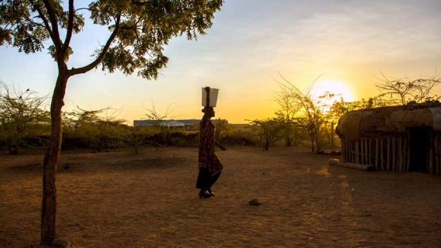 Rose Lekanta, 24 carries water to her home at dawn.