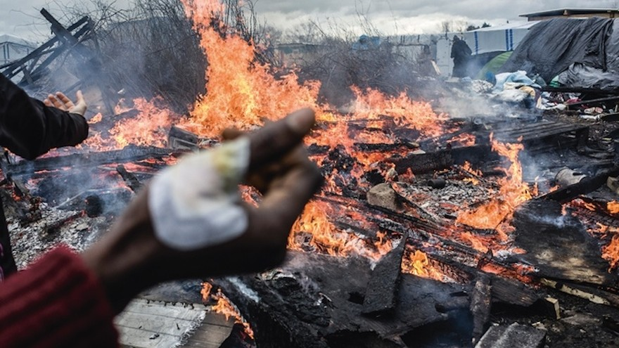 """Calais, France, March 2016: Shelters set ablaze in protest of French government's decision to clear the southern section of """"The Jungle"""" camp"""