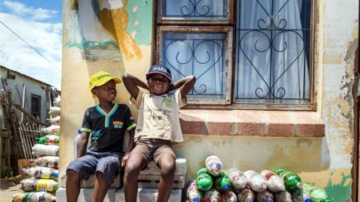 Two small children from Walmer Township in Port Elizabeth sit next to the EcoBricks that have been made for the Penguins Play and learn Centre. Image: https://www.thundafund.com/ecobrickexchange