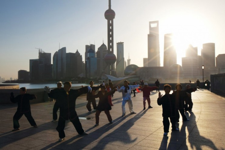 Elderly people practicing Tai Chi Chuan on the Bund as the sun rises over the sk