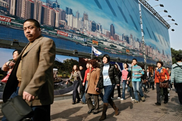 Tourists and passers-by walk pass a giant urban planning billboard on Nanjing Ea