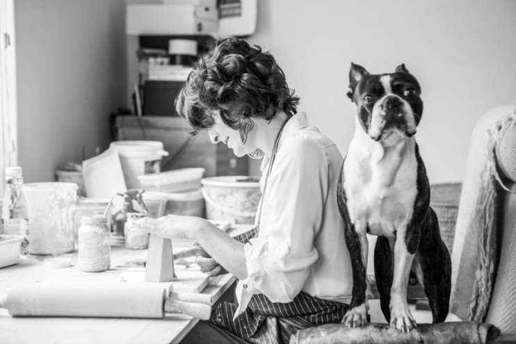Alexia Klompje in her ceramic studio with Bruce Lee her Boston terrier