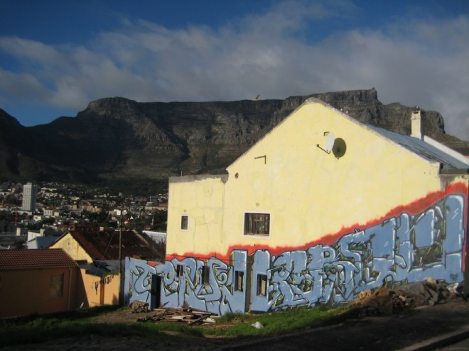 A piece of graffiti by artist Crave Arok set against the backdrop of Table Mountain.