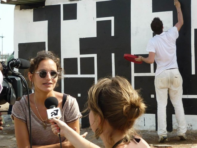 Les Petites Pierres co-founcer Maya Verichon interviewed in front of a mural by street artist Atlas during the 2012 Festival Interference.