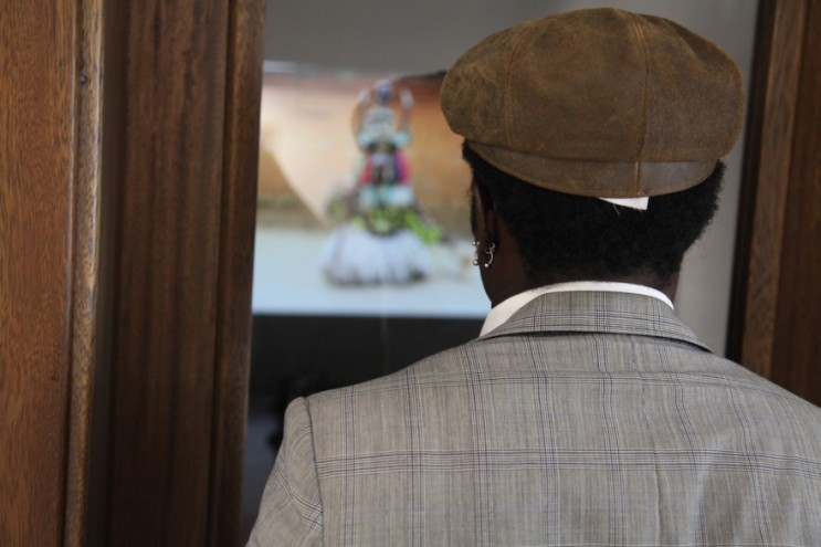 A visitor watches a video piece projected onto the wall in Ken Saro-Wiwa's old office.
