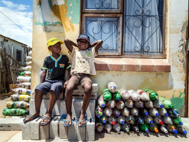 Two small children from Walmer Township in Port Elizabeth sit next to the EcoBricks that have been made for the Penguins Play and learn Centre.