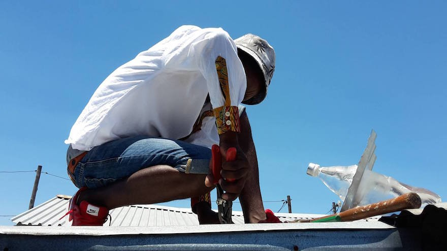Installing a solar light made from an old plastic drinks bottle.