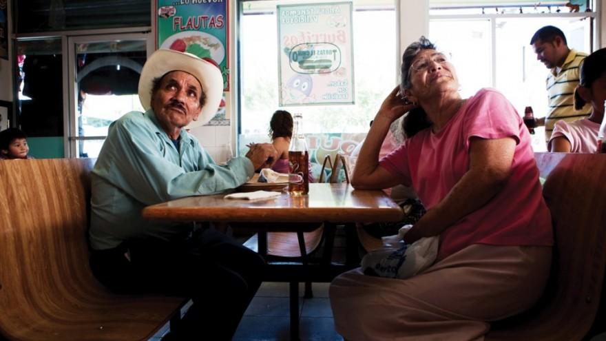 An elderly couple sit down to lunch in a restaurant in Ciudad Juárez. Despite fl