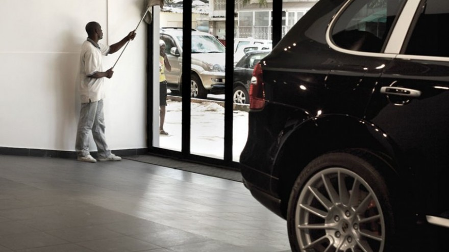 Washing the windows of the Porsche dealership on Avenue Amilcar Cabral in centr