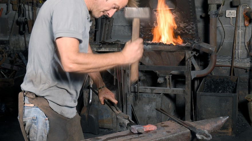 Conrad Hicks at the anvil in his forge. Image: Geof Kirby.
