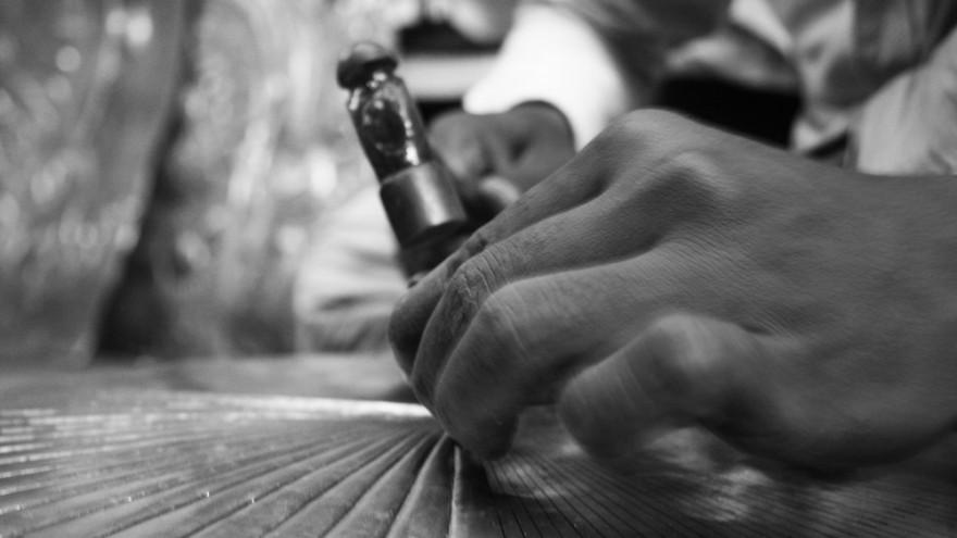 Craftsman working the brass seat of the Tekku Brass stool by Ira Studio.