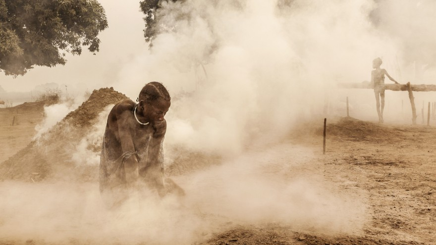 A Mundari woman clears the ground of sticks and dung before the cattle return home from the pastures. Women also milk the animals and look after the children. Image:© Tariq Zaidi / ZUMA Press