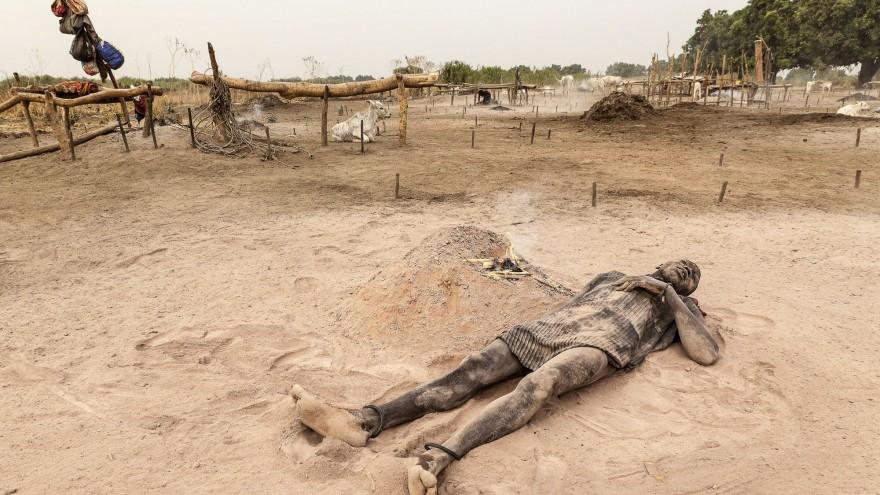 A Mundari man relaxes in the soft, peach-coloured ash and dust of a dung fire. Image:© Tariq Zaidi / ZUMA Press