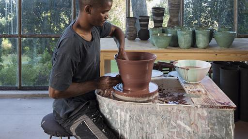 Ceramicist Chuma Maweni works at the potter's wheel at Art In The Forest in Constantia. Image curtesy of Jac de Villliers.