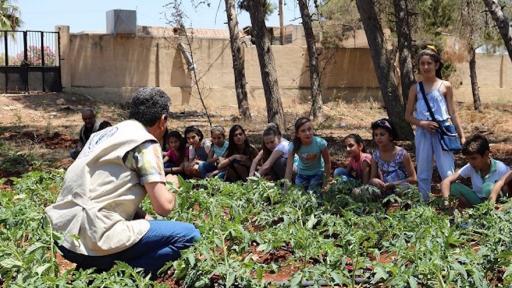 Nutrition education is key. School children and FAO staff discuss nutrition at a school garden in Hama, Syria. ©FAO/Wajdi Skaf