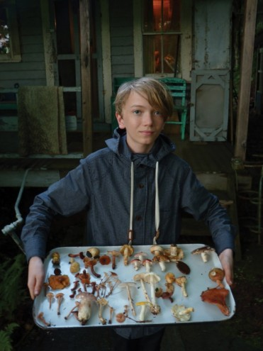 Young hunter, Leander Johnson poses with mushroom specimens in front of the old