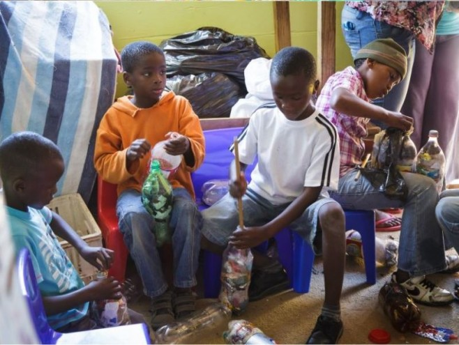 Young boys in Walmer Township take part in the community effort involved in making EcoBricks.