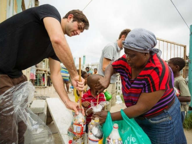 A woman from Walmer Township in Port Elizabeth is making EcoBricks with an EcoBrick volunteer.