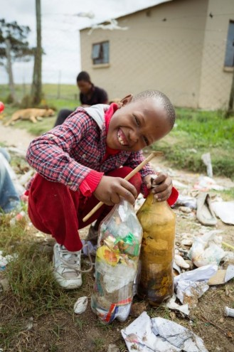 A young boy from Walmer Township displays his contribution to the EcoBricks project.