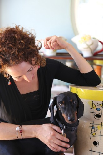 Kate Rosenberg resting her elbow on one of her hand-built stools, with her dachshund Oliver and her hand-built jugs in the background along with her collection of work by Imiso Ceramics and Light from Africa/Art in the Forest. Image: Inness Mass.