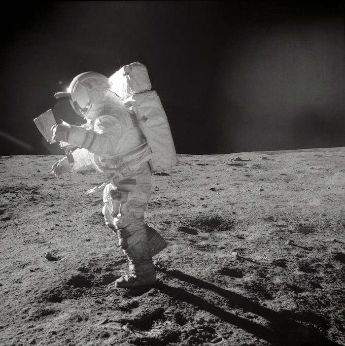 Astronaut Edgar D. Mitchell, Apollo 14 Lunar Module pilot, moves across the lunar surface as he looks over a traverse map during extravehicular activity (EVA). Lunar dust can be seen clinging to the boots and legs of the space suit. Image: NASA