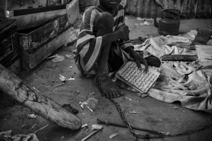 A young talibe bound by chains in an isolation area of a daara in the city of Touba, May 27, 2015. In this daara the youngest talibes are shackled by their ankles to stop them from trying to run away.