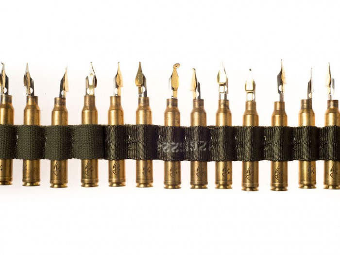 Laser etched 300 win mag bullet cartridges, speed ball pen nib, section of number 2 pencil, nylon and canvas straps, staples.