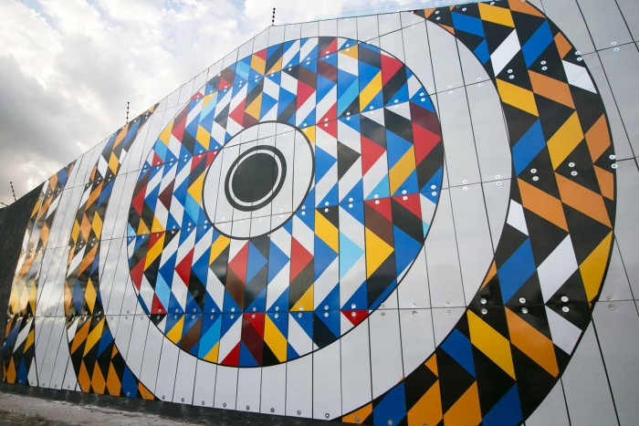 r1's latest street art made up of 180 multi-colored chevron signs, 500 reflective vinyl stencils, 400 drilled holes installed onto a wall 11 X 6 meters.