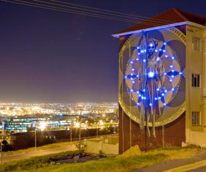 Harvest mural by Faith47 lit up at night. Photo by Rowan Pybus @Makhulu_