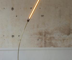 This brass and walnut wood lamp sways gently, mimicking a blade of grass in the wind.