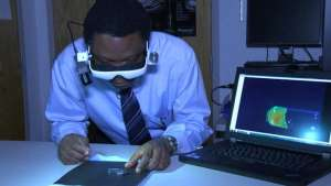 Dr. Samuel Achilefu demonstrates his cancer visualisation glasses.